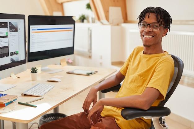 Portret van afrikaanse man zittend op een stoel voor computermonitoren en glimlachend in de camera werkt hij als softwareontwikkelaar