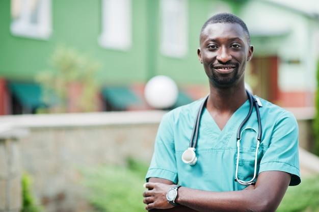 Portret van afrikaanse mannelijke arts met een stethoscoop die groene jas draagt