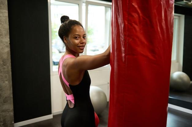 Portret van afrikaanse sportvrouw, aantrekkelijke vrouwelijke bokser in zwarte sportkleding die door haar schouder naar de camera kijkt, lacht schattig poserend in de buurt van een bokszak op boksschool. gezonde levensstijl concept