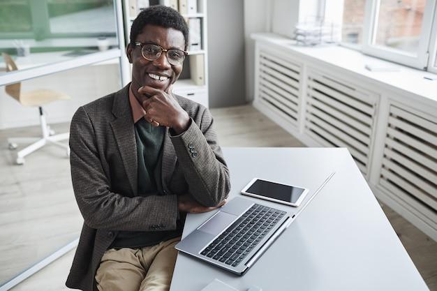 Portret van afrikaanse succesvolle manager glimlachen tijdens het werken aan de tafel op laptop