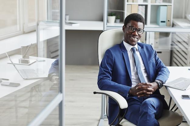 Portret van afrikaanse succesvolle zakenman lachend zittend op een stoel op kantoor
