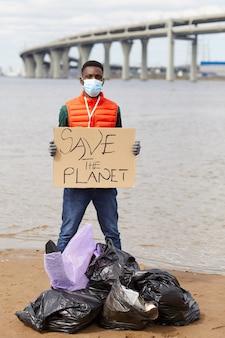 Portret van afrikaanse vrijwilliger in beschermend masker met aanplakbiljet terwijl hij dichtbij de vuilniszakken dichtbij de rivier staat