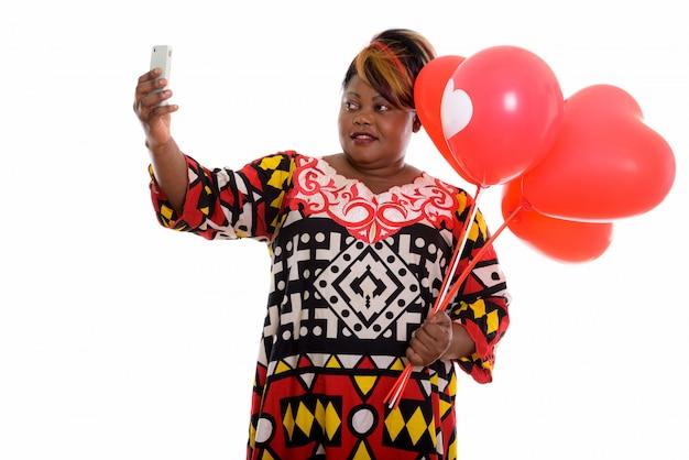 Portret van afrikaanse vrouw met ballonnen en het nemen van selfie