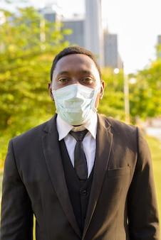 Portret van afrikaanse zakenman die masker draagt bij het park in de stad