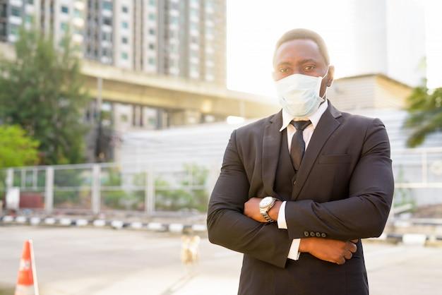 Portret van afrikaanse zakenman die masker met wapens dragen die in de stadsstraten worden gekruist