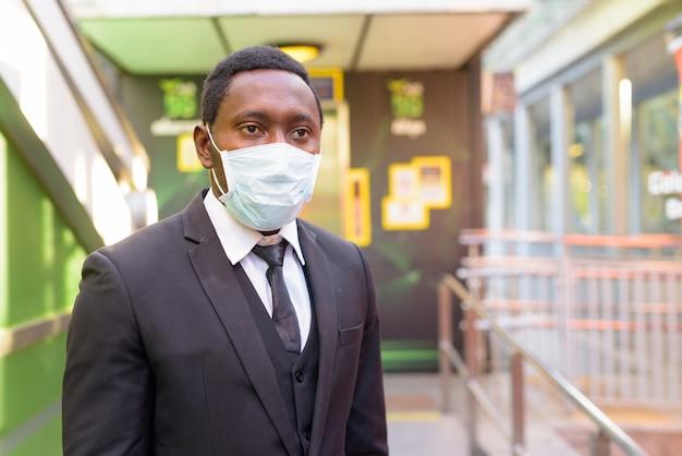 Portret van afrikaanse zakenman die met masker bij het station in openlucht denken