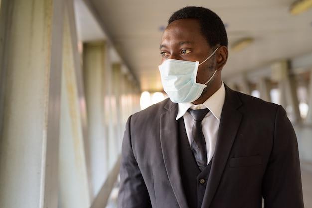 Portret van afrikaanse zakenman die met masker mening van de stad bij de voetgangersbrug bekijken