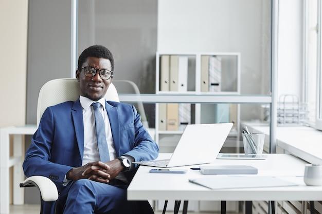 Portret van afrikaanse zakenman in pak zittend op een stoel op zijn werkplek en op kantoor