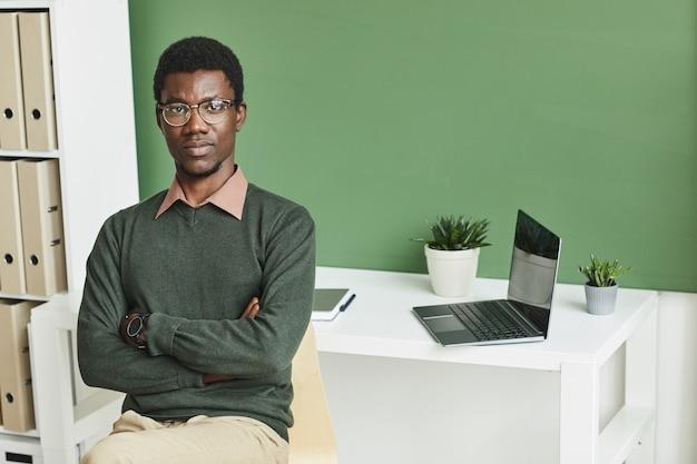 Portret van afrikaanse zakenman in vrijetijdskleding die zich met wapens bevinden die op kantoor worden gekruist