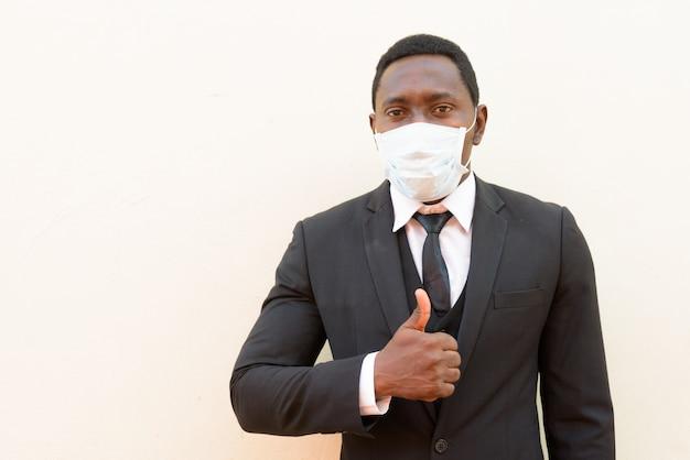 Portret van afrikaanse zakenman met masker dat duimen opgeeft tegen witte achtergrond