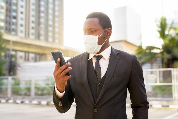 Portret van afrikaanse zakenman met masker die telefoon in de stadsstraten gebruiken