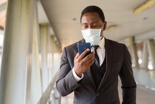 Portret van afrikaanse zakenman met masker die telefoon met behulp van bij de voetgangersbrug