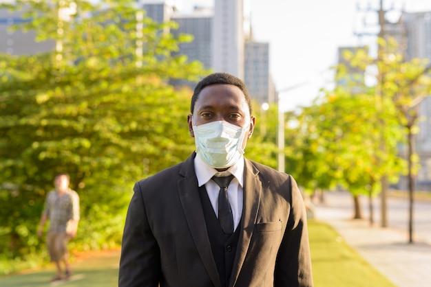 Portret van afrikaanse zakenman met masker in het park in de stad