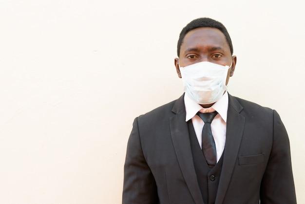Portret van afrikaanse zakenman met masker tegen een witte achtergrond