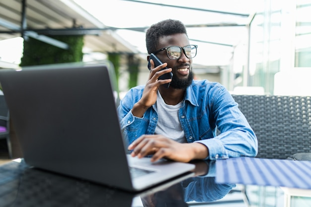 Portret van afrikaanse zakenman praten aan de telefoon met laptop voor hem op tafel