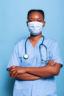 Portret van afro-amerikaanse arts-assistent met beschermend gezichtsmasker