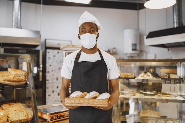 Portret van afro-amerikaanse bakker met vers brood bij de bakkerij. banketbakker die klein gebakje houdt.