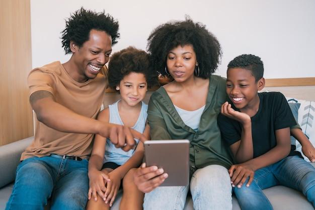 Portret van afro-amerikaanse familie die een selfie samen met digitale tablet thuis neemt. familie- en levensstijlconcept.