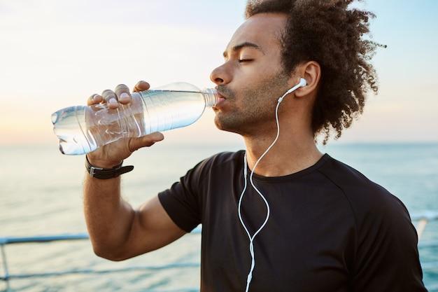 Portret van afro-amerikaanse fit atleet drinkwater uit plastic fles met koptelefoon op close-up. zich verfrissen met water en een zwart t-shirt dragen
