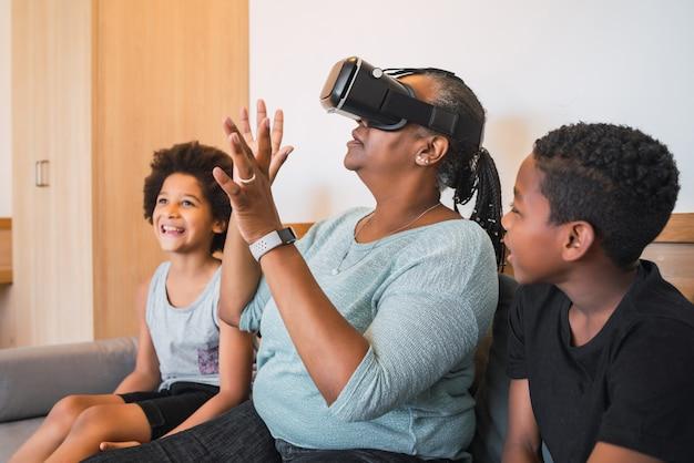 Portret van afro-amerikaanse grootmoeder en kleinkinderen spelen samen met vr-bril thuis