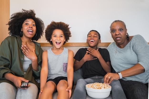 Portret van afro-amerikaanse grootmoeder, moeder en kinderen kijken naar een film en popcorn eten zittend op de bank thuis. familie en levensstijlconcept.