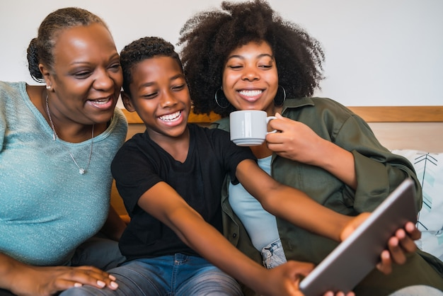 Portret van afro-amerikaanse grootmoeder, moeder en zoon die thuis een selfie met digitale tablet nemen. technologie en levensstijlconcept.