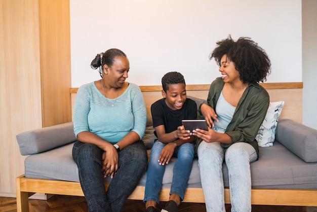 Portret van afro-amerikaanse grootmoeder, moeder en zoon met behulp van digitale tablet thuis