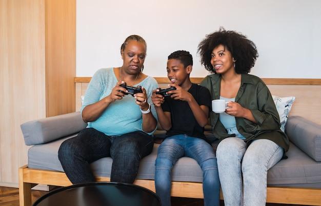 Portret van afro-amerikaanse kind dat grootmoeder en moeder leert hoe ze de joystick moeten gebruiken om videogames te spelen. technologie en levensstijlconcept.