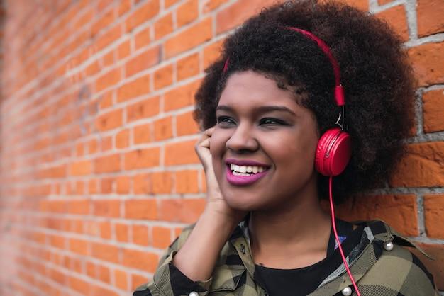 Portret van afro-amerikaanse latijns-vrouw glimlachend en luisteren naar muziek met koptelefoon tegen bakstenen muur. buitenshuis.