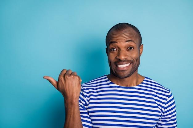 Portret van afro-amerikaanse man punt duim copyspace geïsoleerd over blauwe achtergrond