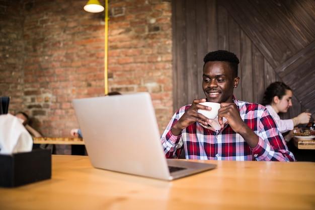Portret van afro-amerikaanse man zit in een café en werkt op een laptop.