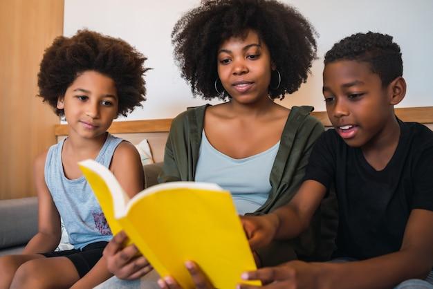Portret van afro-amerikaanse moeder die een boek leest aan haar kinderen thuis. familie en levensstijlconcept.
