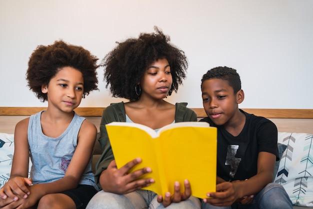 Portret van afro-amerikaanse moeder die een boek leest aan haar kinderen thuis.