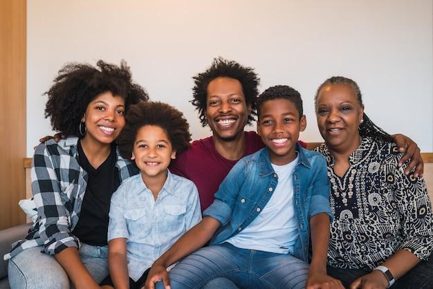 Portret van afro-amerikaanse multigenerationele familie camera kijken terwijl zittend op de banklaag thuis. familie en levensstijlconcept.