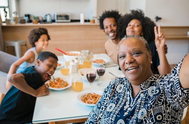 Portret van afro-amerikaanse multigenerationele familie die samen een selfie neemt tijdens het diner thuis.