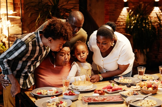 Portret van afro-amerikaanse oma die kaarsen blaast terwijl ze verjaardag viert met familie in gezellige ...