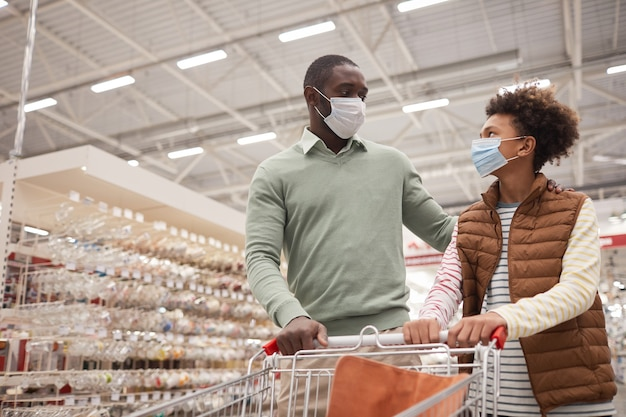 Portret van afro-amerikaanse vader en zoon die maskers dragen in de supermarkt terwijl ze een winkelwagentje trekken, kopieer ruimte