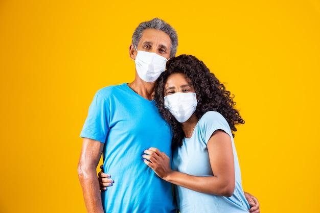 Portret van afro-amerikaanse vader met dochter die masker draagt. vader en dochter dragen masker ter bescherming van covid 19, quarantaine. blijf thuis concept. vaderdag!