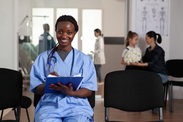 Portret van afro-amerikaanse verpleegster zittend op een stoel in de wachtruimte van het ziekenhuis