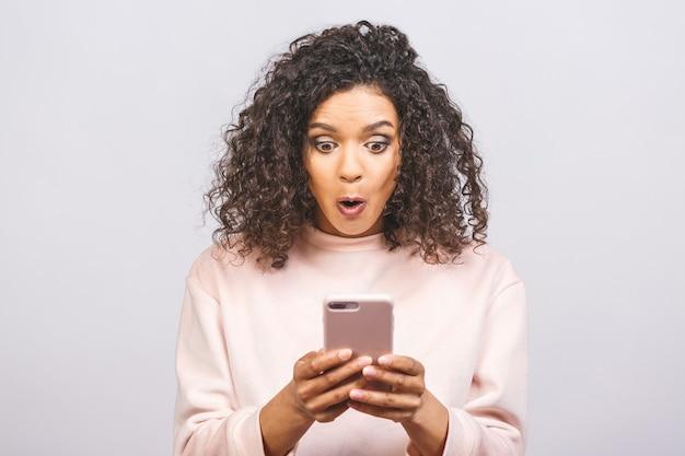 Portret van afro-amerikaanse verrast aantrekkelijk meisje met behulp van nieuw apparaatgadget