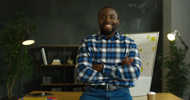 Portret van afro-amerikaanse vrolijke knappe man in bont shirt staande in kantoorruimte en vreugdevol glimlachen naar de camera.