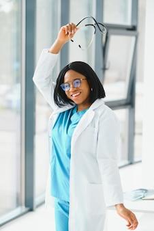 Portret van afro-amerikaanse vrouw arts glimlachend in het ziekenhuis