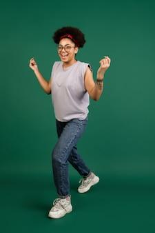 Portret van afro-amerikaanse vrouw geïsoleerd op groene muur met copyspace