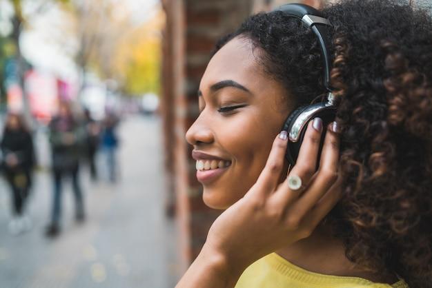 Portret van afro-amerikaanse vrouw glimlachend en luisteren naar muziek met een koptelefoon in de straat. buitenshuis.