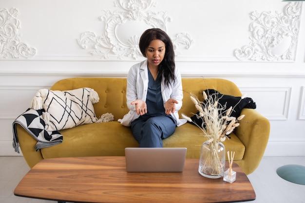 Portret van afro-amerikaanse vrouwelijke arts die laptop computer online overleg met behulp van
