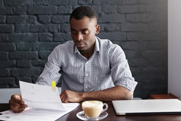 Portret van afro-amerikaanse zakenman in geruit overhemd onderzoekt nauw stuk papier in zijn handen