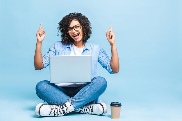 Portret van afro-amerikaanse zwarte vrouw in casual zittend op de vloer in lotus houding en met laptop geïsoleerd op blauwe achtergrond