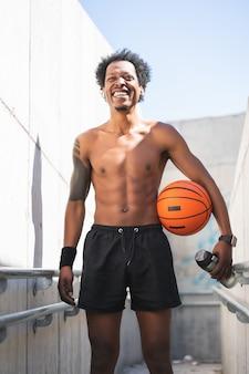Portret van afro atleet man met een basketbal bal en ontspannen na training buitenshuis. sport en een gezonde levensstijl.