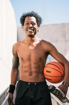 Portret van afro atleet man met een basketbal bal en ontspannen na training buitenshuis