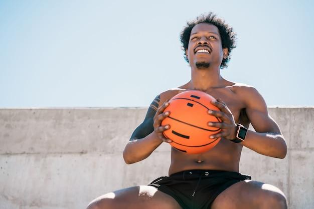 Portret van afro atleet man met een basketbal bal zittend buiten. sport en een gezonde levensstijl.